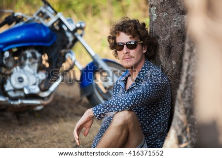 Young handsome man with curly hair sitting under big tree, his stylish motorbike on the background - stock photo