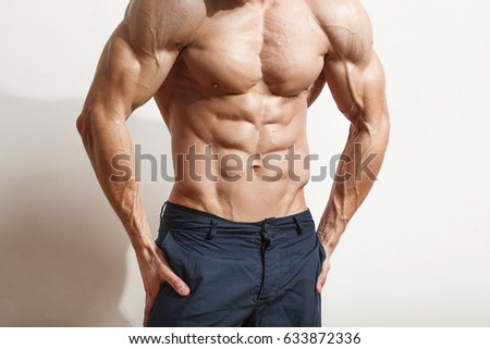Young handsome man with great physique posing over white background