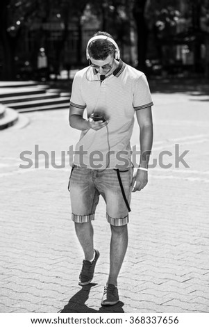 young handsome man with headphones and smart phone walking on street in summer, black and white photography - stock photo