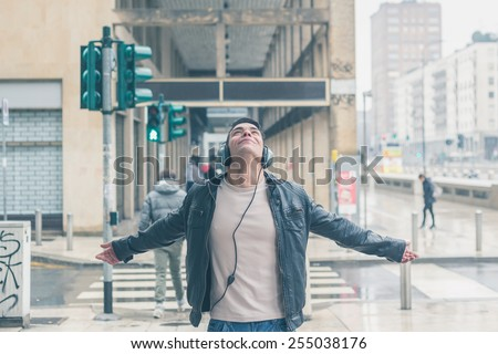 Young handsome man with headphones listening to music in the city streets - stock photo