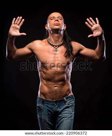 Young handsome man with naked torso on a dark background - stock photo