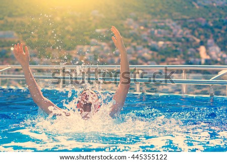 Young handsome man with raised arms in the pool, sunlight. Toned