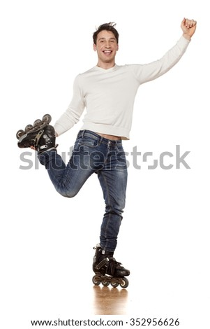 young handsome man with roller skates posing in the studio
