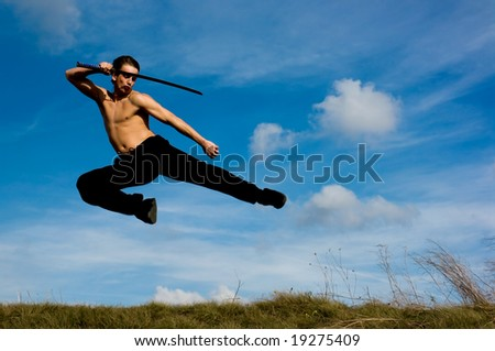 Young handsome man with samurai sword jumping against blue sky.