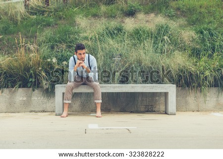 Young handsome man with short hair and beard wearing suspenders and sitting on a concrete bench