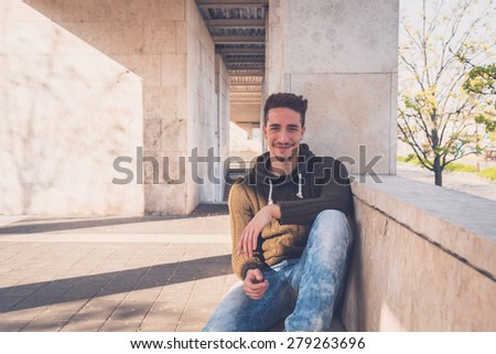 Young handsome man with short hair posing in an urban context - stock photo