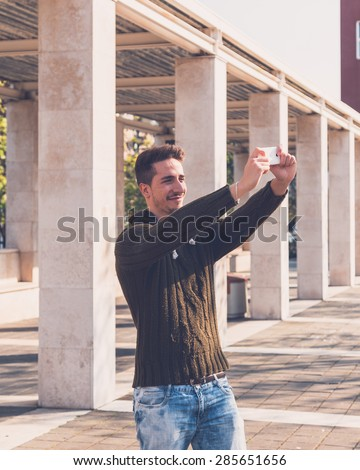 Young handsome man with short hair taking a selfie in an urban context