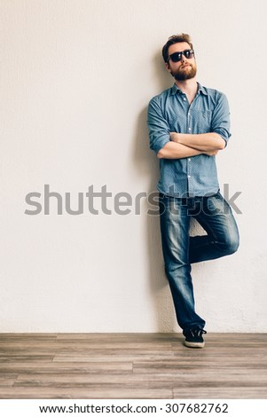 Young handsome man with sunglasses, leaning against a white wall. Hands crossed. - stock photo