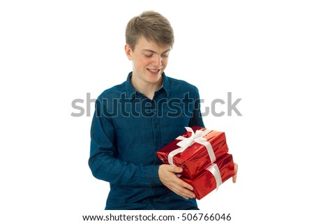 young handsome man with two gifts in hands looking on it and smiling isolated on white background