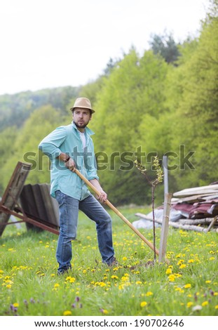 Young handsome man working with hoe in his backyard garden