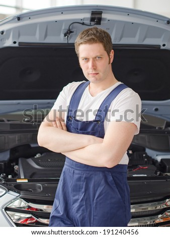 Young handsome mechanic standing near open car hood
