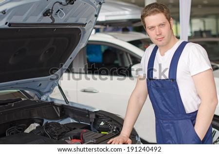 Young handsome mechanic standing near open car hood - stock photo