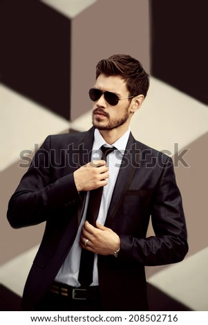 Young handsome men on creative background with sunglasses - stock photo
