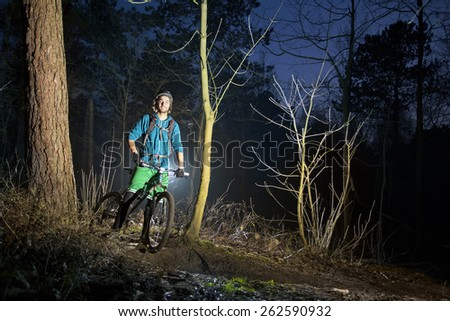 Young, handsome mountain biker smiling and posing on an off road trail at dusk, standing on his bike, wearing a helmet, shorts, as well as the proper protection: gloves, knee protectors,  - stock photo