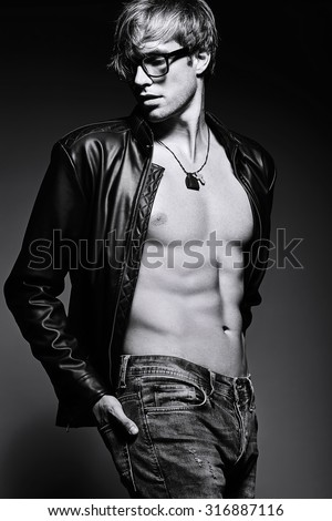 Young handsome muscled fit male model man posing in studio showing his abdominal muscles - stock photo