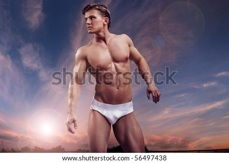 Young handsome muscular guy over twilight sky - stock photo