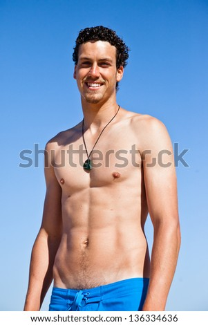Young handsome muscular man in a bathing suit hanging on the beach. Surfer type.
