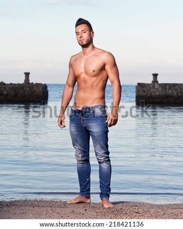 Young handsome muscular man on the stony beach. - stock photo