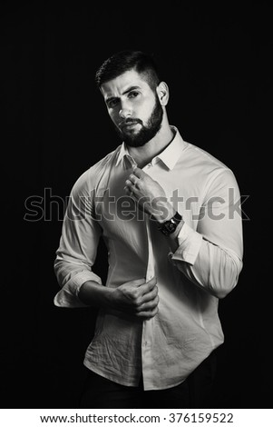 Young handsome muscular man with a beard, posing on a black background - stock photo