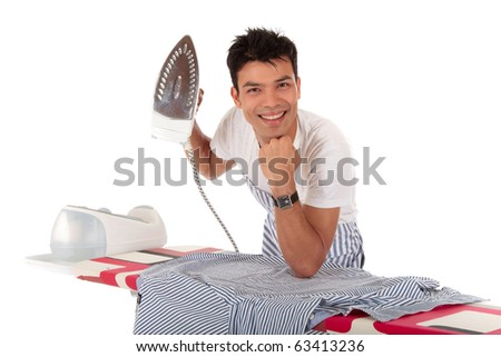 Young handsome Nepalese man against the ironing-board with iron in one hand. Studio shot, white background. - stock photo