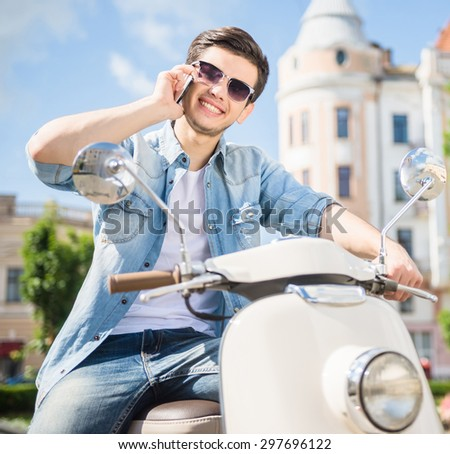 Young handsome nifty man sitting on scooter and using phone. - stock photo