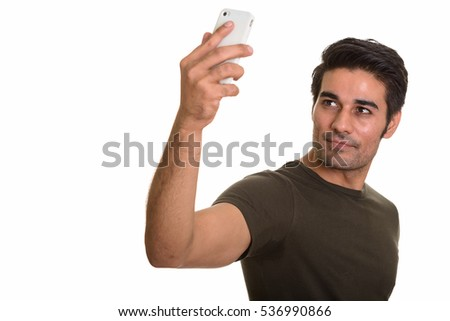 Young handsome Persian man taking selfie with mobile phone