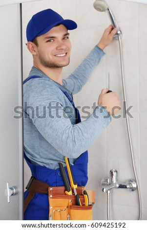 Young handsome plumber working in shower stall