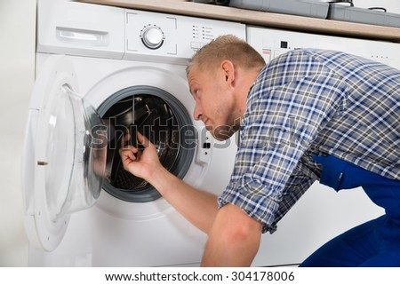 Young Handsome Repairman Repairing Washer In Kitchen