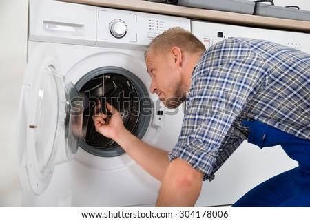 Young Handsome Repairman Repairing Washer In Kitchen - stock photo