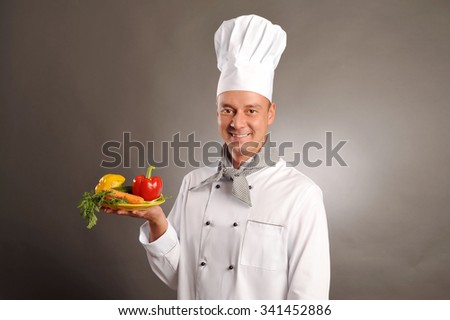 young handsome smiling chef holding vegetables on grey background - stock photo
