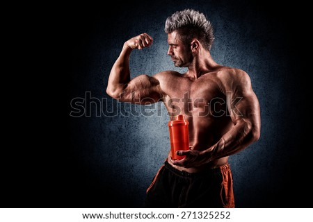 young handsome sporty man in the studio with a bottle in his hand