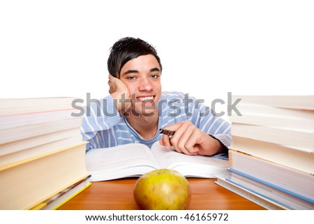Young handsome student smiles happy and sits between study books at desk. Isolated on white. - stock photo