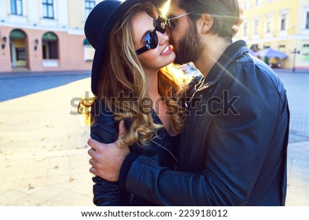 Young handsome stylish guy listing her pretty blonde girlfriend, romantic sensual couple hugs on the street of european city at bright evening sunlight, rock n roll styled clothes and sunglasses. - stock photo