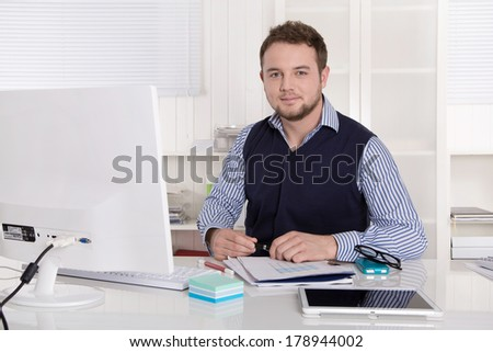 Young handsome successful accountant at desk at office.