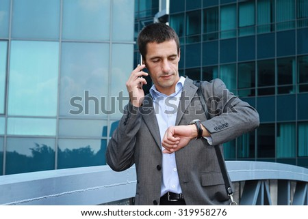 Young handsome, successful businessman talking on the phone in the city, in front of modern building. Businessman in a hurry looking at his watch - stock photo