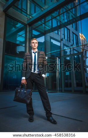 Young handsome successful stylish businessman standing near modern office building. Concept: victory.