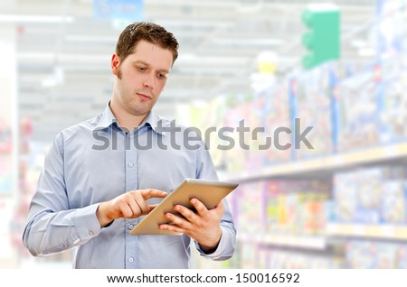 Young handsome supervisor with tablet pc in the mall - stock photo