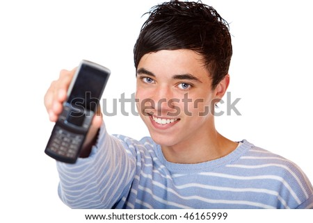 Young handsome teeanger smiles happy and holds mobile phone into camera. Isolated on white.