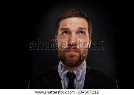 Young handsome thoughtful business man has idea, studio over black background - stock photo
