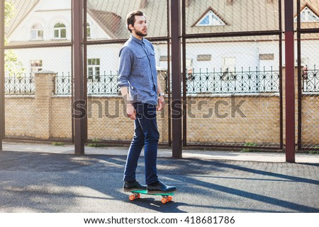 Young handsome thoughtful trendy hipster bearded man riding a skateboard, long board on the playground