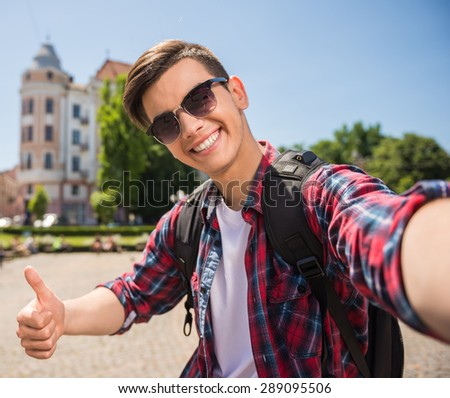Young handsome tourist making selfie in the street of old european city. - stock photo