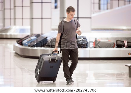 Young handsome traveller man in 20s leaving arrivals lounge of airport terminal building after collecting his baggage at conveyor belt, using smartphone app in public wifi area, messaging - stock photo