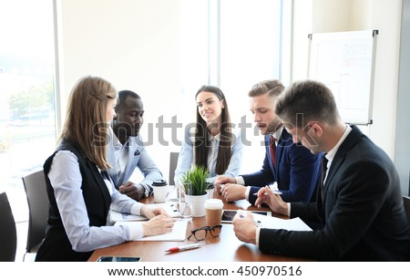 Young handsome woman gesturing and discussing something while his coworkers listening to him sitting at the office table - stock photo