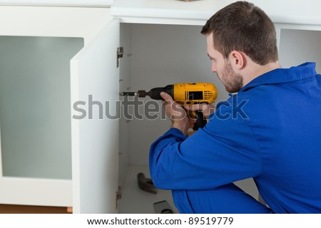 Young handyman fixing a door in a kitchen - stock photo