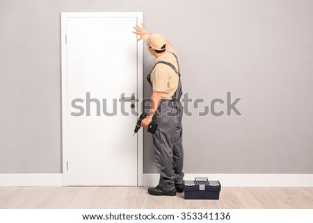 Young handyman installing a white door with an electric hand drill in a room - stock photo