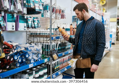 Young handyman or DIY homeowner in a store standing selecting a product in the hardware department and reading the label - stock photo