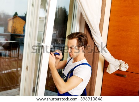 Young handyman repair window with screwdriver - stock photo