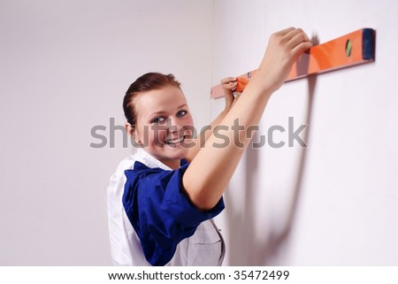 young handywoman looking at her water level - stock photo