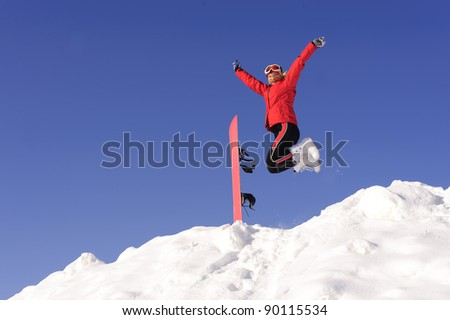 Young happy active woman jumping in snow