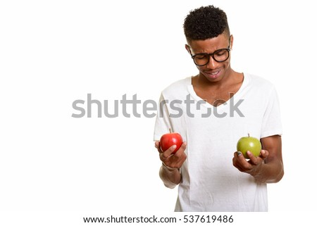 Young happy African man choosing between red and  green apple